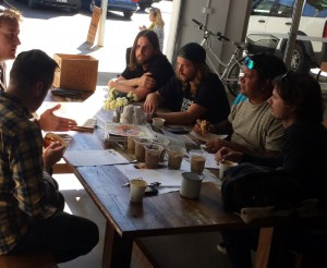 Brewers and artists seated at a table with beer ingredients
