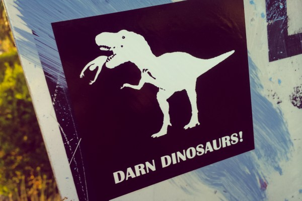 "sticker that says, ""darn dinosaurs"" and has picture of t-rex eating a human"
