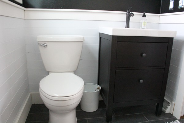 Toilet surrounded with white planked walls