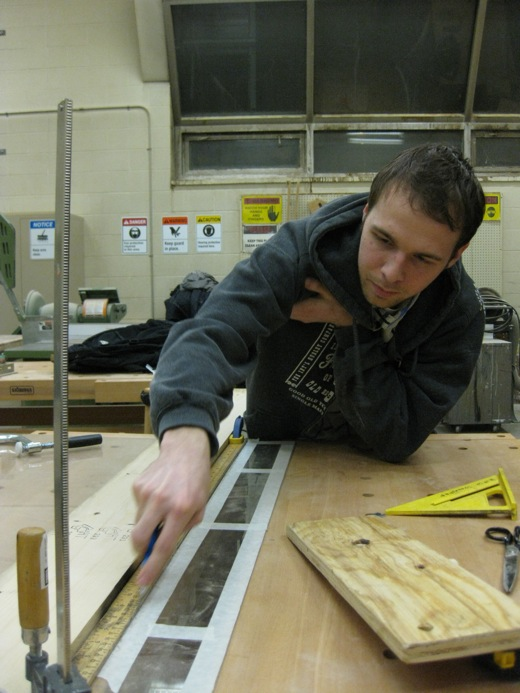 Josh begins scoring the plexiglass