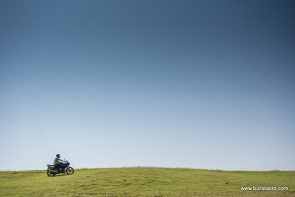 bulleteer akash jain riding a hero karizma atop a hill in the grasslands of pagara