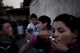 "A group of young men play with a weapon while they smoke""pasta base""( a very cheap and addictive drug made with cocaine left overs)"