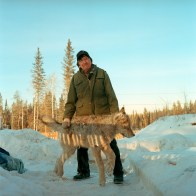 Elder Wilfred GrandJambe, 72, stands for a photo with a frozen wolf he had snarred and shot the day before outside Fort McKay.