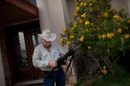 Mike Vickers checks his rifle outside his house. Vickers carries several weapons with him at all time. (Dominic Bracco II/ Prime For The Washington Post)