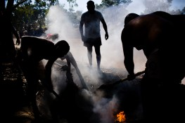 "An emu is placed in the ground and surrounded with hot coals to be cooked traditionally on the banks of the Darling river. The Darling is central to the Barkindji culture, a means of survival and identity. The term Barkindji is thought to translate to ""river people"". David Maurice Smith/Oculi."