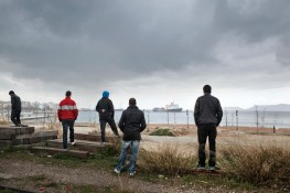 2012. Corinth. Greece. Young migrants from North Africa near the Port of Corinth looking at the cargo ship they hope to illegally board later that night. In Corinth, a small sea town on the Peloponnese, the boarding of boats directly is attempted by group of North Africans who have established themselves in an old train station.