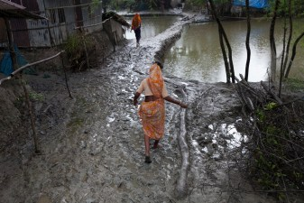 A woman walks along a muddy street at Gabura in Satkhira.