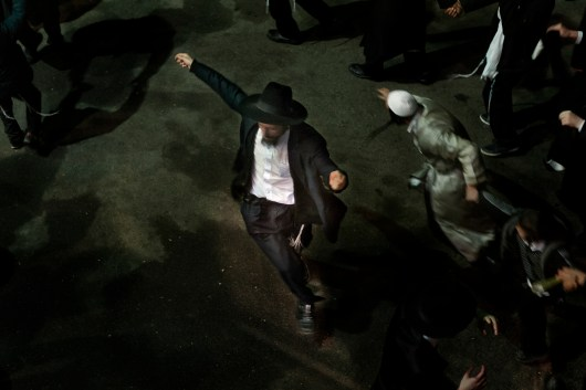 A pilgrim dances to Klezmer music on the last night of the pilgrimage. Approximately 30,000 religious Jews make an annual pilgrimage to the tomb of Breslover Rabbi Nachman's tomb in Uman, Ukraine for Rosh Hashanah. The pilgrimage is unique because it attracts men from across the spectrum of Judaism. In making the pilgrimage, they believe that Rabbi Nachman will intercede on their behalf on Yom Kippur, the Jewish day of atonement.