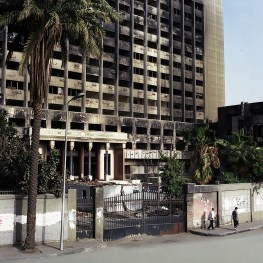 Two men pass by the remains of what used to be the National Democratic Party's landmark-torched on January 28th, 2011 during the escalations that came to topple Hosni Mubarak.