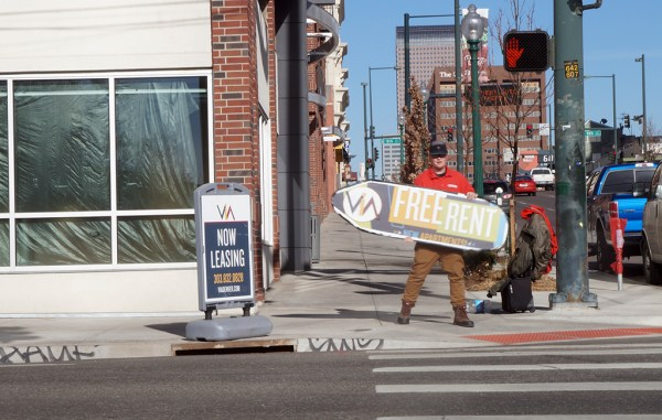 A sign spinner outside of an apartment building in Denver advertises a rent discount. (Aaron Kremer)