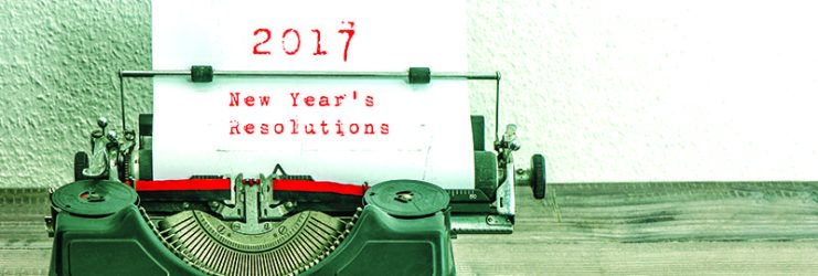 Typewriter with white paper page on wooden table. sample text 2017 New Year's Resolutions. vintage style toned picture