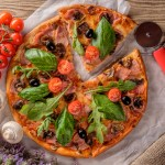 Delicious fresh pizza with mushrooms and bacon on a wooden background. Top view.