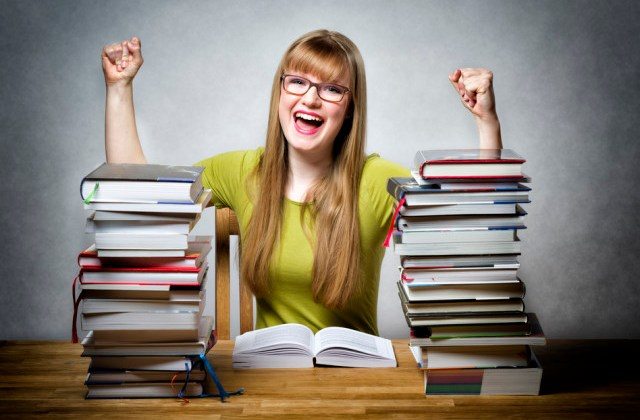 young happy schoolgirl with glasses and lots of books at a table