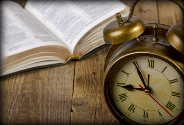 open Holy Bible with clock on wood