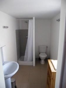 Salle d'eau avec douche, lavabo, WC et étagère de rangement