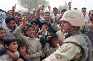 Jubilant Iraqis cheer U.S. Army Soldiers at a humanitarian aid compound in the city of Najaf.