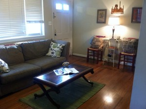 Furniture that doesn't take up much space, such as a coffee table with thin legs and a glass-topped, neutral-colored entry table, help make my tiny living room appear more spacious.