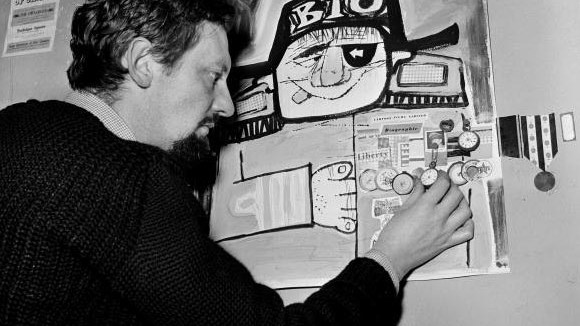 1957 London, England. Animation and Film. The office of a cartoon film unit. Cartoonist Bob Godfrey adds a watch to a poster on the wall of his studio.