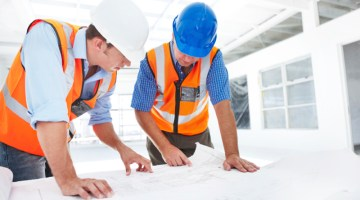 Two construction workers checking the architectural plans before they start the building project