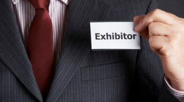 Businessman Attaching Exhibitor Badge To Jacket, exhibitors, trade show, event, exhibit, exhibition, expo, tradeshow,
