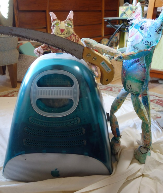 Funny cat doll trying to saw open a vintage iMac.