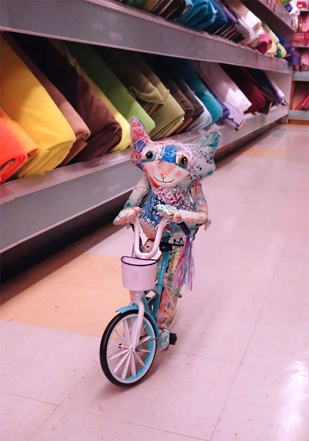 The Chairman peddles his bicycle down an aisle of Joanns Fabric store.