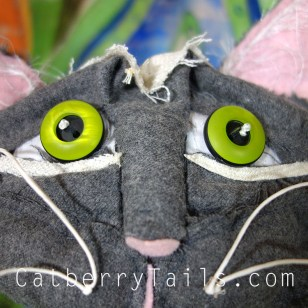 Closeup of the new gray magnificat with adorable button eyes and fabric sculpted face.