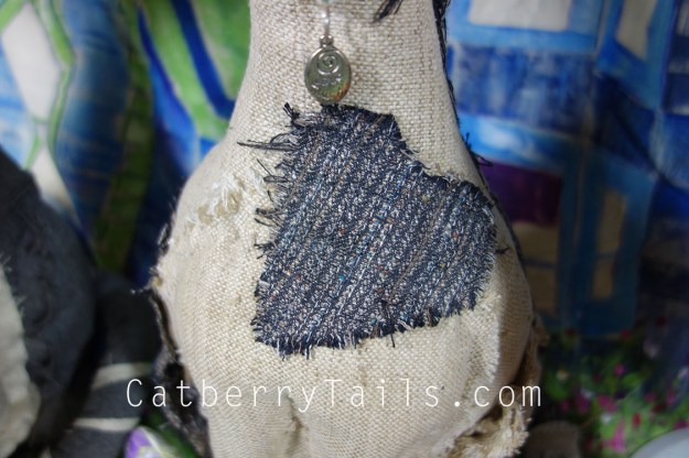 Closeup of a tweed heart patch on the chest of the Opie Doll Magnificat.