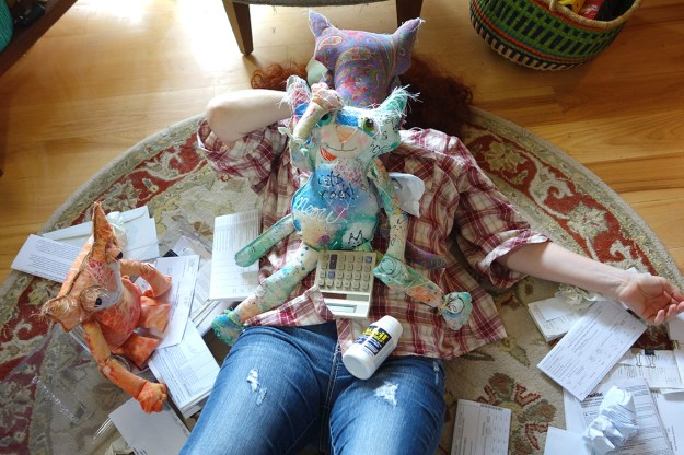 The Kreatrix flat out on her back surrounded by papers, a calculator, a bottle of Advil and the cat doll community.
