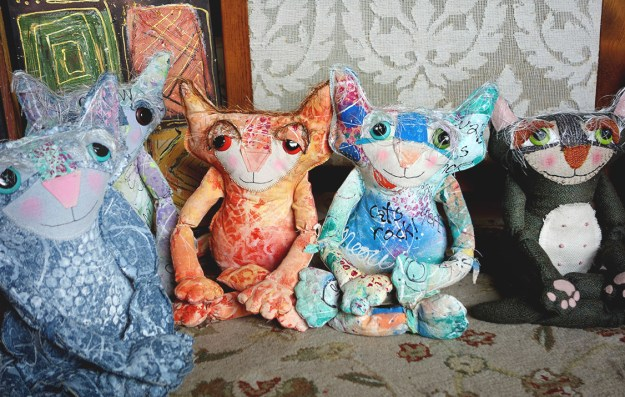 A row of cute, colorful cat dolls sits crossed legged as they meditate.