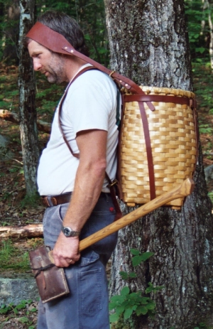 A photo of a man carrying an ax and a large basket using a tumpline. His posture is thrown way off.