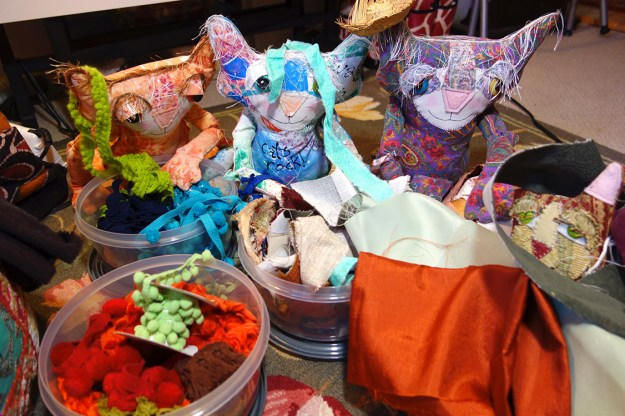 Whimsical cat dolls gathered around fringe and fabric, trying pieces of it on.
