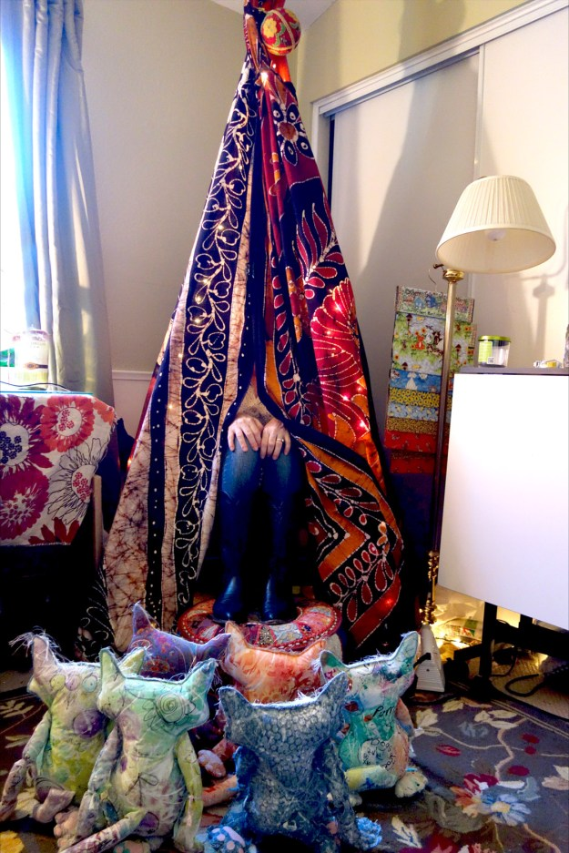 Cat dolls are sitting in front of an indoor tepee. All we see of the Kreatrix is her legs sticking out.
