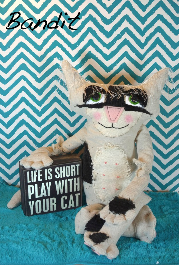 Adorable soft sculpture cat doll with large black velvet spots. He sits on a turquoise rug with turquoise and white wallpaper in the background. He poses with a sign that reads: life is short. Play with your cat.