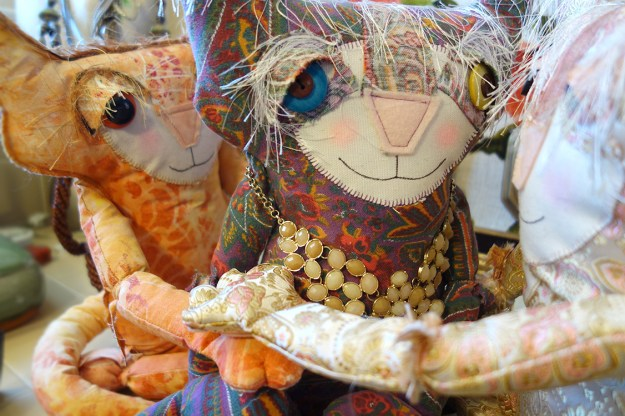 Three soft sculpture cat dolls and in a group embrace.