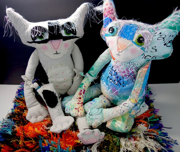 Two of the soft sculpture cat dolls are sitting on a rug trying to meditate. Their mouths have been altered in photoshop to show extreme concentration.