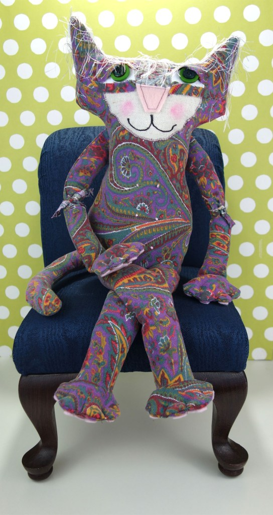 Penny, the adorable soft sculptured cat doll, sits with her legs crossed on a navy blue doll chair.