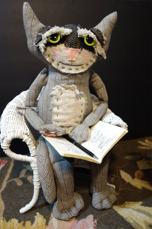 Very cute soft sculpture cat doll named Rascal sits in a chair with a pad and pen just like a shrink would do when treating a patient.