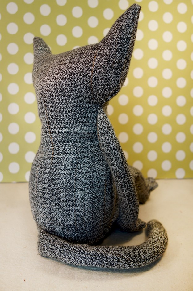 A brand new soft sculpture cat is featured in a photograph. He is seated with with his back to us and his tail wrapped around. He's made out of a man's charcoal grey tweed suit.
