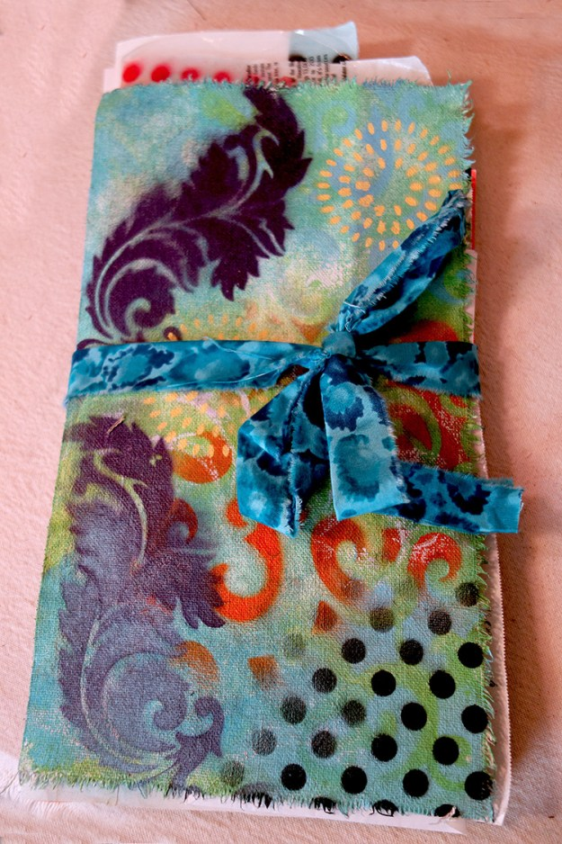 Very colorful, large hand painted journal with a ribbon tied around it.