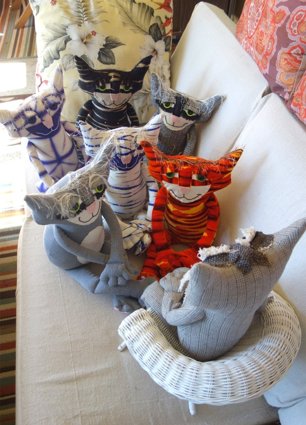 Adorable soft sculptured cat sits in a small wicker chair with a group of cats gathered at his feet.