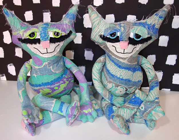 Two very cute cats seated with crossed legs. They are made from raw silk marbled fabric.