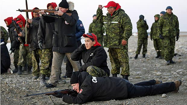 Prime Minister Stephen Harper, on the ground, and Defence Minister Rob Nicholson, standing centre, shoot .303 Lee Enfield rifles while taking part in a demonstration with Canadian Rangers near the Artic community of Gjoa Haven, Nunavut Tuesday.