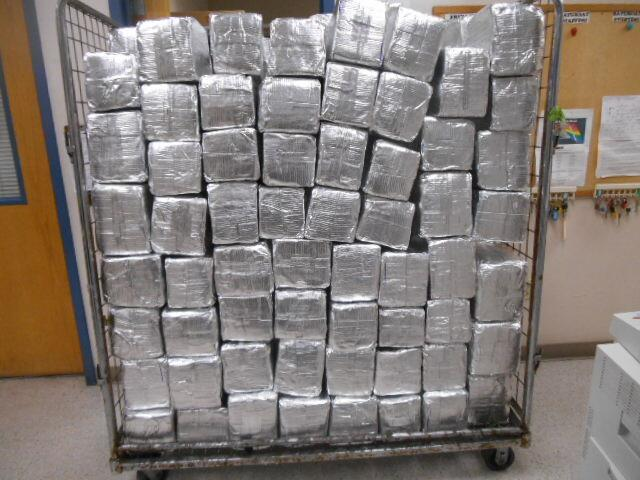 Packages containing 1,303 pounds of marijuana seized by CBP officers at World Trade Bridge in Laredo, Texas in a shipment of mud floor tile