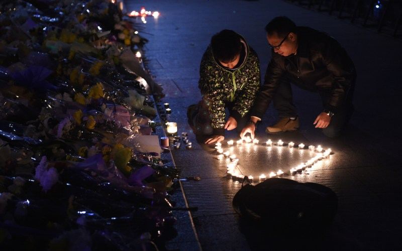 Two men place candles in the shape of a heart at the site of a New Year's Eve stampede at The Bund in Shanghai on January 1, 2015. AFP PHOTO / Greg BAKER