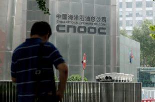 2016年上半年,中国海洋石油有限公司净亏77.4亿元,出现2001年上市以来首次中期业绩亏损。图为2016年7月29日,一名男子站在中海油位于北京的总部的大门前。(STR/AFP/Getty Images)