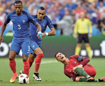 cristiano ronaldo grimaces on the ground after a clash with france s dimitri payet second left ...