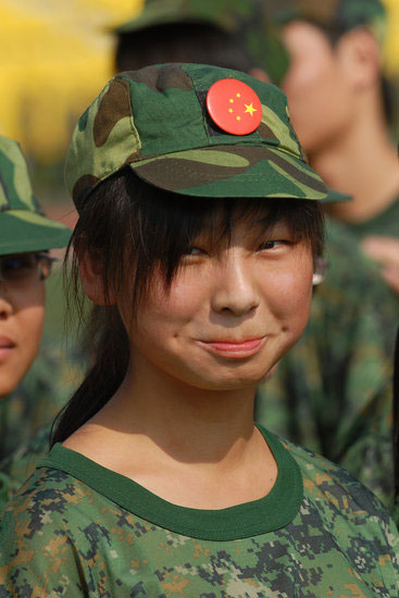 Chinese student with China flag pin on her hat during military training.