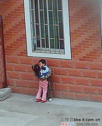 Two Chinese kids kissing next to a brick wall.