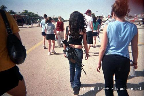 A Jewish girl carrying a machine gun on the streets of Israel.